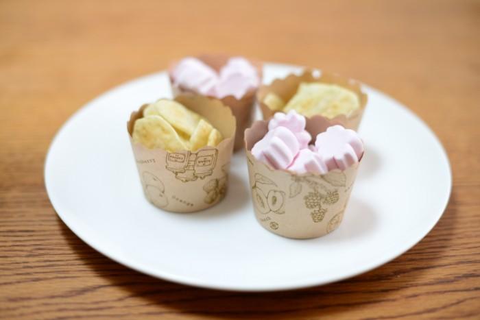 100均にある手作りカップケーキの容器は、可愛らしくバリエーションも豊かで、かつ小分けにできるので、市販のお菓子を盛り付けるのに便利です。  今回は、ふんわり優しい桜の風味が楽しめる桜の花エキス入りの、桜の花を形どったマシュマロ、桜えびのおせんべいを市販で購入し、カップケーキ容器に盛り付けました♪
