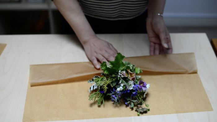1.準備するもの  ・ワックスペーパー(花束の丈に対して縦1.5倍×幅2倍の大きさのもの) ・アルミホイル(茎の1/3が隠れる大きさ) ・キッチンペーパー ・リボン又は麻紐  2.準備したキッチンペーパーを、花束の茎に巻き、お水を吸わせます。  3.茎に巻いたキッチンペーパーを包むようにお水が外に漏れないようにアルミホイルを巻きます。  4.ワックスペーパーでお花を包みます。  ・ワックスペーパーをテーブルの上に広げます。 ・ワックスペーパーの中央にブーケを上から2cm程下に下げて置きます。上を2cmあけるのは花がワックスペーパーの内側に花が収まる様に保護するために下げます。 ・ワックスペーパー下の部分をアルミホイルが隠れる位置までブーケとは垂直に折り曲げます。 ・ワックスペーパーの両端を中央に向かって丸くブーケに沿わすように包みこみます。 ・麻紐をとめたあたりで、ワックスペーパーをしぼってリボン又は麻紐で結びます。