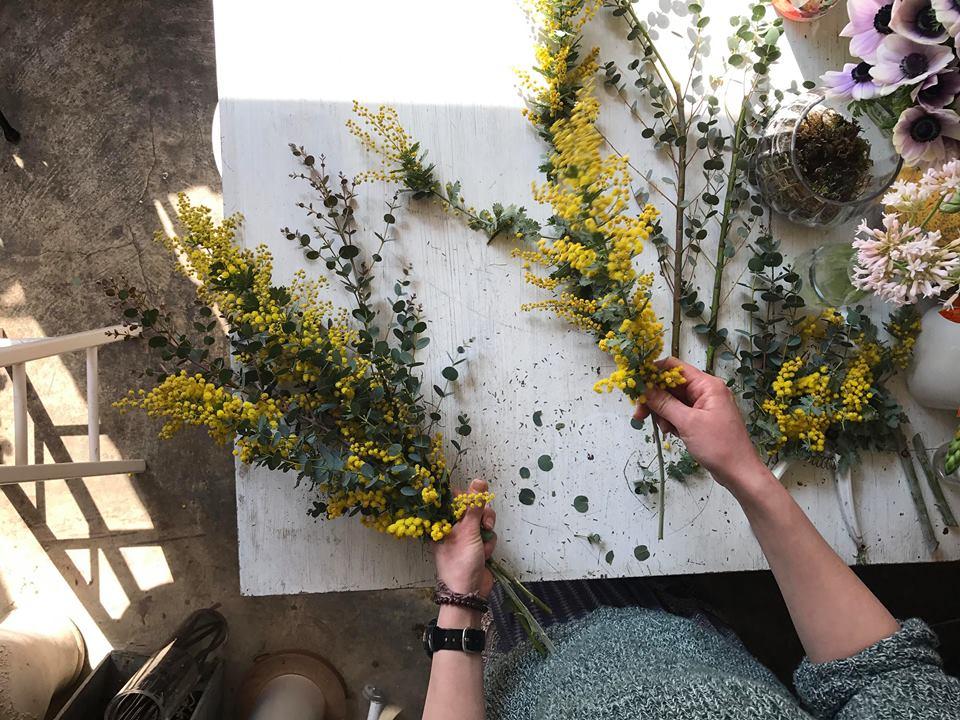 ①手で持つ部分のお花や葉は取り除きます。ミモザとユーカリを交互に組んでいきます。
