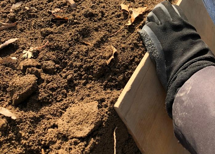 5. 畝が「金の延べ棒」の形になるように、板(鍬)を使って側面の土を押さえる。