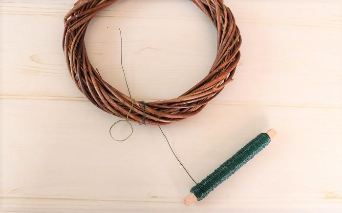 今回は20㎝のリース台を使います。ワイヤーで、つるす時のためのわっかをはじめに作っておきます。  その隣にリース用のワイヤーを2~3回リース台に巻き付けます。ワイヤーのはじっこは、最後にまとめるために長めに残しておきましょう。