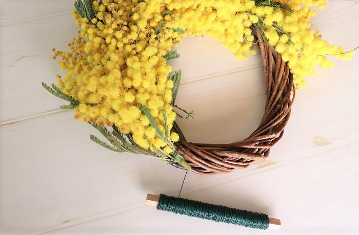 ひとつ前に巻き付けたワイヤーの位置に次のミモザの花の部分が重なるように、少しづつ位置をずらしてワイヤーで順々に巻き付けていきます。