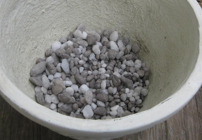 寄せ植えの水はけを良くするために、鉢の底に鉢の高さの1/5ほど入れます。大粒の赤玉土でも代用できます。  鉢底用の石は、排水口ネットなどに入れてから鉢の底にセットすると植え替えの時に再利用しやすいです。  つぶすと粉状になり、使い終わった後には土壌改良剤の役割をするような鉢底用の石もあります。