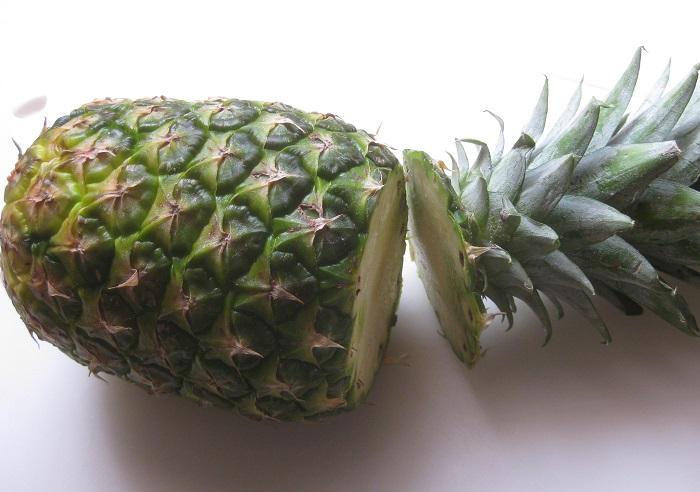 普通、パイナップルは芯の部分が非常に固くて食べられません。なので切り方といえば、皆様おおよそこんなイメージですよね。  まず、葉を切り落とします。(葉の根元を持ってぐるっとねじってはずす方法もあります。) この写真は普通のパイナップルです。