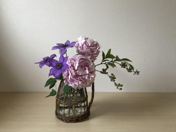 4.クレマチスの位置が決まったら、もう一本の芍薬を生け込みます。  はじめの芍薬はアレンジ全体の中心となる花になります。  もう一本は最初の芍薬より少し蕾の花を選び、上の位置に生け込みます。  小さめの花を選ぶ事によって、芍薬のボリューム感を少し軽やかにし自然植生を感じる生け方になり飾られている様子に安定感が出て来ます。