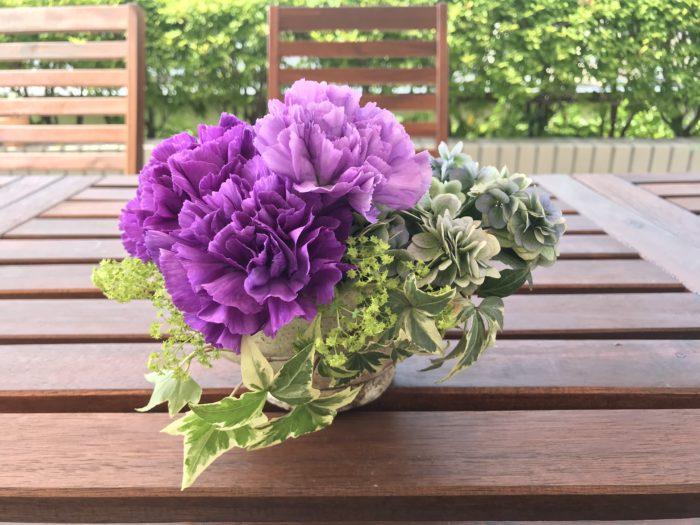 6.アルケミラモリスをバランス良く配置します。  山紫陽花とアイビーの間に自然になじませる様に生け込み、カーネーションの下にも少しだけあしらいます。  この場合は花を入れ過ぎない事がポイントです。  入れ過ぎない事によってアルケミラモリスの小さなお星様みたいな様子が引き立ち、カーネーションの名前でもあるムーンダストの名前のごとく、深い夜空のような色合いに小さな星が瞬くイメージで生けてみて下さい。