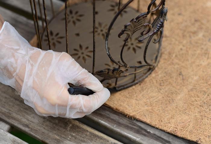 鳥かごをココヤシマットの上に置き、底の形をペンでなぞります。