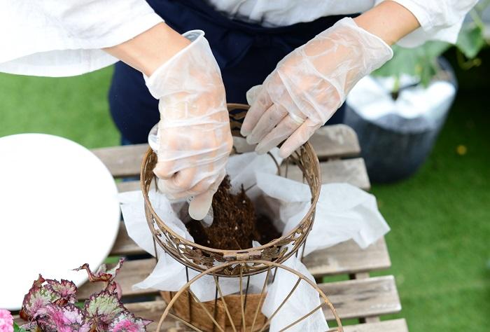 ココヤシマットの上に不織布を敷き、不織布のはじを何ヵ所かかごの外に引っ張り出します。不織布の上に、肥料入り培養土を底面が見えなくなるくらい入れます。