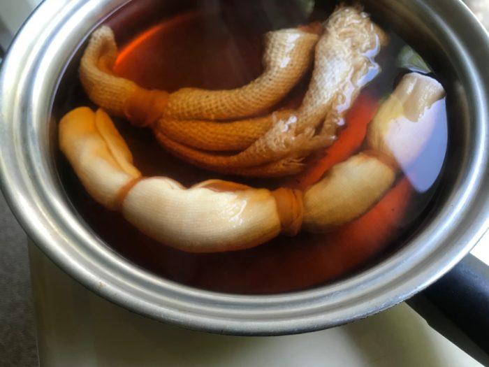 6.鍋から玉ねぎの皮を取り出し、下準備で輪ゴムを縛ったハンカチを鍋に入れて20分程火にかけます。  \むらなく染めるポイント/ 鍋に入れる前にハンカチ全体を水で濡らしておきます。染めるハンカチを水につけておく事によって布全体をむらなく染める事ができます。