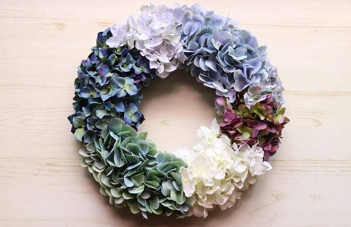 毎年、あじさいの季節になるとアーティフィシャルフラワーで作ったあじさいのリースを飾ります。  アーティフィシャルフラワーは直射日光や雨風にはそれほど強くないので室内に飾ることをおすすめしますが、その季節限定と決めて玄関ドアに飾ってとても美しいです。2~3シーズンくらいなら問題なく綺麗に使えると思いますよ。だんだんと色があせてきますが、それもアンティーク風として楽しめばいいかなと思います。  リース台やグルーガンは、最近では100均でも購入できます。初めての方は小さいリースからぜひ作ってみて下さい。