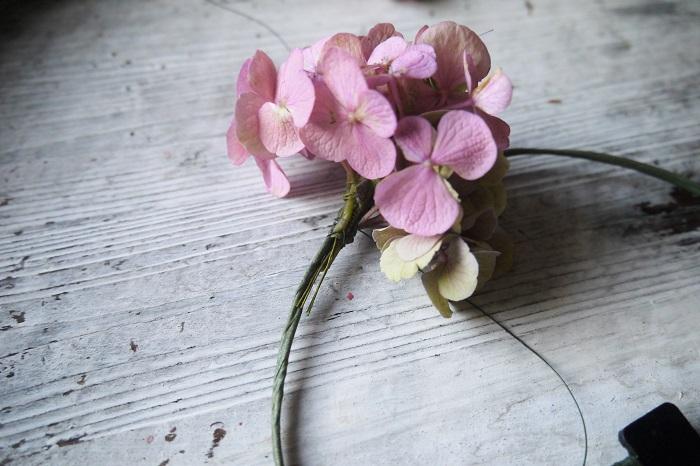 いよいよ丸く形作ったワイヤーにお花を留めていきます。  食事を済ませて、水分も補給して取り掛かりましょう。リースは編み始めから編み終わるまで同じペースで編んでいきます。途中でペースが変わると、全体のボリュームやバランスが崩れてしまうからです。途中休憩は取りません。