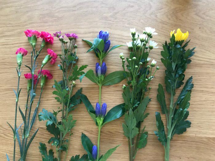 先ほど用意した基本の3本に、少し鮮やかなピンクの色合いの2本の花を加えて、5本の花を使用します。加えたお花は、スプレーカーネーションと小菊です。