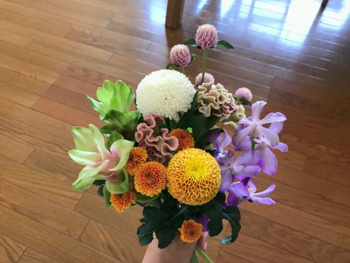 バランスよく、最初に大きなピンポンマムを手に持ち、大きい花、小さい花と順番に合わせて行きます。  少しずつ高低差をつけて行くと合わせやすいと思います。意識して後ろ側の花を高くして前に向かって行くに従い低く合わせてみましょう。全部の花を手で合わせたら、手に持っている支点を麻紐や輪ゴムで止めます。  ここで花を止める事によって、花瓶に生けた時に形を崩さずに生ける事が出来ます。