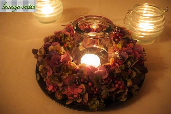 リースの内側にキャンドルホルダーをセットしてテーブルに置いて楽しみます。優しいキャンドルの明かりを、アジサイのお花で囲むように。  お部屋の明かりを消して、キャンドルを点して過ごす時間。自分へのご褒美として、こんな風にゆったり過ごすリラックスタイムを作ってみませんか。  アンティークカラーのアジサイのリースがあれば、そんな自分へのご褒美タイムをさらに素敵に演出してくれます。