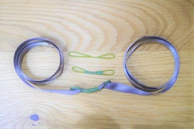 まず、手首に巻くベースとなる部分から作ります。  ①#20ワイヤーを5㎝くらいにカットし、3~4㎝程度の幅を確保して両側を丸めて輪を作ります。  ②作った輪にリボンを通して、フローラルテープで固定します。こうすることでリボンが動かなくなるので、装着したときに安定感が出ます。