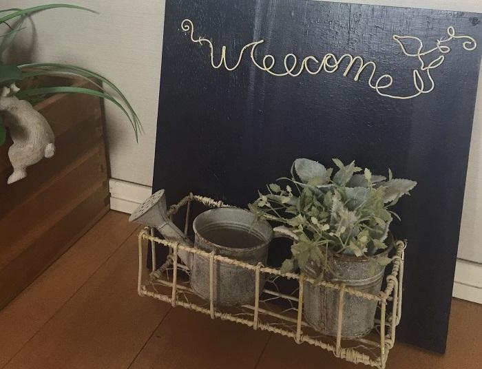 Photo by:杉井志織  Welcomeの文字と、花鉢を飾るバスケット部分をワイヤーで作ったウェルカムボード。玄関やベランダに飾るのにぴったりです。