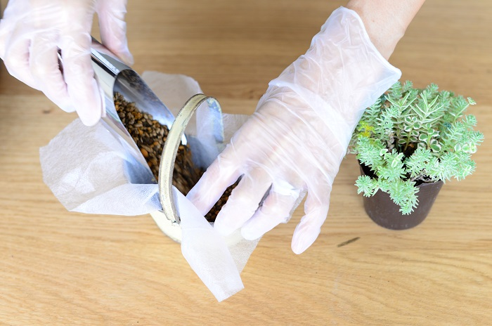 ブリキの器に、不織布を敷いて培養土を器の高さの1/3くらい入れます。  (不織布は、土もれ防止とブリキの器の劣化防止のため使いましたが、無しでも作ることができます。)