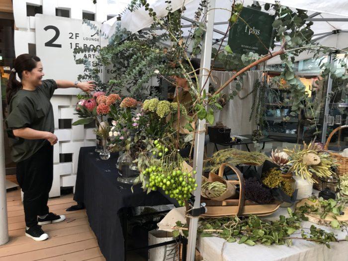 花教室、展示会装花、オリジナルワイヤー花器の制作など、幅広く活動中のフラワースタイリスト増田由希子氏のショップ。  今回の出店のコンセプトは秋という季節の中で「カーキ&ブラック」を色のテーマとして、フラワースタイリストの増田由希子さんとスタッフの女性のお二人もシックで落ち着いたカーキ&ブラックのスタイリングで植物と調和したファッショに身を包み、ブース全体の雰囲気をシックに秋色でまとめ上げ、美意識の高さが際立つf plusさん。  今回お取り扱いの植物で一番のポイントは?とお伺いした所、秋色でシックである植物をご用意したという事と、すべてドライフラワーとして長く楽しむ事が出来る生花にこだわり、今回の秋の出店を楽しんでいらっしゃいました。オリジナルの花器なども制作中、シンプルながらセンスと個性が光る植物を引き立てる花器も魅力です。