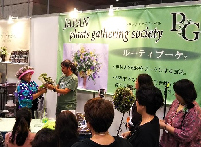 プランツ・ギャザリングⓇは、根っこのついた花やグリーンをやさしく丁寧に組み合わせて「小さな花束」(ユニット)を作り、器に植えこむ園芸技術で、「寄せ植えギャザリング」「花ギャザリング」ともいわれています。プランツ・ギャザリングⓇの考案者である青木英郎氏もご来場されていました。