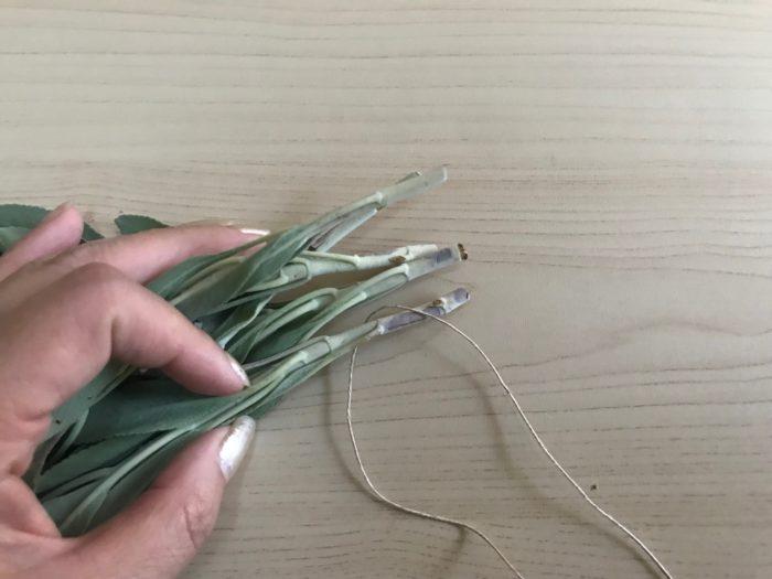 束ねたら、紐を巻き付けていきます。一本の茎に紐をかけます。