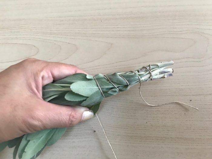 紐をかけたら、らせん状に葉の先まで、ホワイトセージをまとめる様にギュッと巻き付けていきます。