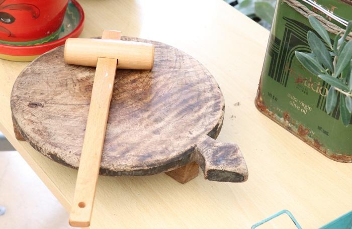 オリーブの渋を抜く時、種抜き器で種を取ったり、ナイフで種に当たるまで3か所くらい切り込みを入れるのですが、岡井先生はオリーブ生産地の方に教わって木づちで実に割れ目を入れるそうです。  写真の木の板と木づちは、オリーブの実を一粒一粒つぶして割れ目を入れる時に使う岡井先生のお気に入り。木の板は、使われていなかったチーズのカット台をもらってきて磨いて磨いてきれいにしたものを愛用しているそうです。本物のアンティーク、とてもあたたかい気持ちになりますね。