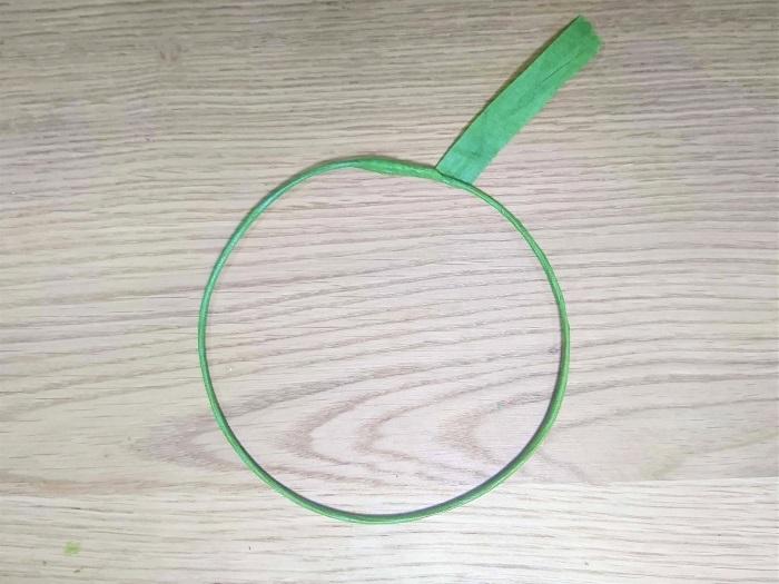 #20ワイヤーにフローラルテープで巻き付け、Φ12~13㎝の円になるように丸めます。  ※フローラルテープを巻きつけておいた方が、テープの粘着力で花材が安定しやすくなります。  ※円を作るには、手ごろなサイズのお皿などに巻き付けると、きれいな円が作れます。