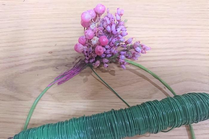 さらにエリカを置いて、きゅっきゅっと2回ワイヤーで締めます。  この作業を1周繰り返していきます。粒々した可愛いエリカの花を黙々と編んでいく、とても幸せな時間です。