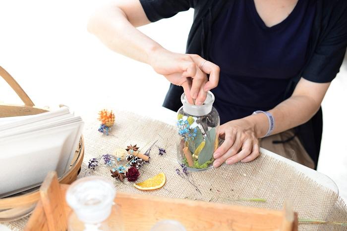 その場で、きれいなドライフラワーやドライフルーツを瓶に詰めている様子。色とりどりのドライフラワーを取り扱っているので見ているだけでわくわくします。