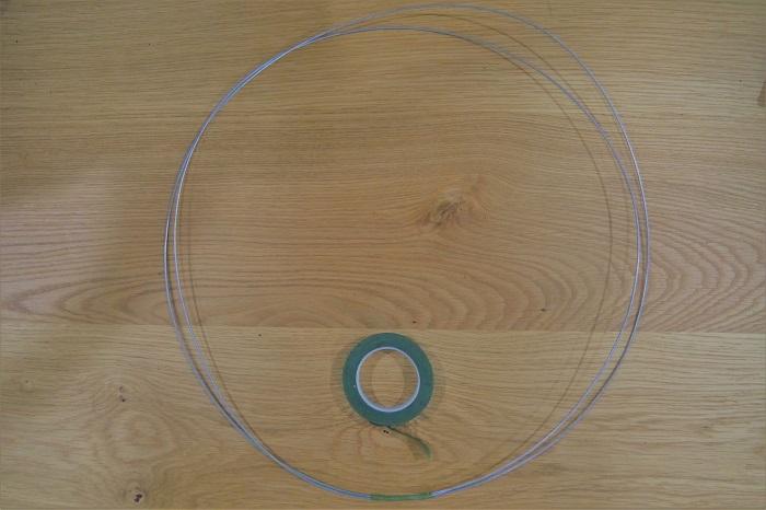 スチールワイヤーで、Φ50㎝くらいの輪を作ります。大きな鉢などに巻き付けると、きれいな輪が出来ます。1.6㎜のスチールワイヤーにこだわる必要はありません。ある程度丈夫で形を作りやすいワイヤーであれば、問題ありません。  輪の形が出来たら、フローラルテープで巻きます。これは、地のワイヤーの色を目立たなくする為と、グリーンの枝をベースに留めやすくする為です。