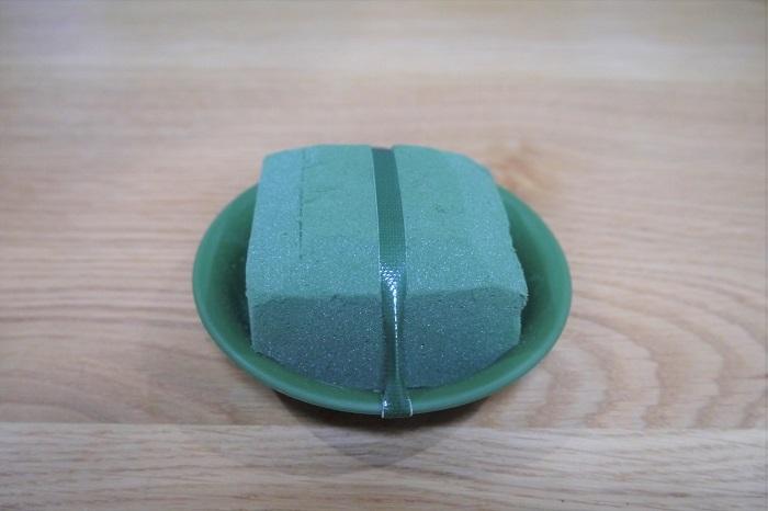 3号パオ皿にフローラルフォームをセットして、動かないように防水テープを1周させて固定します。フローラルフォームを固定させたパオ皿を、水を張ったバケツに静かに沈めます。この時、無理に水に沈めないように。フローラルフォームは水を吸って自然に沈んでいきます。