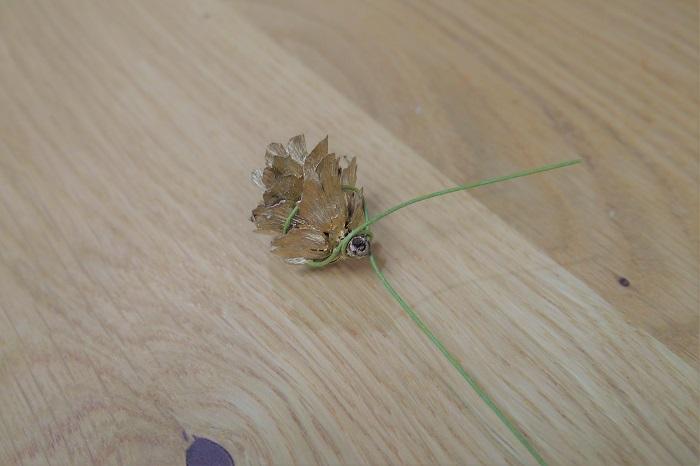 木の実たちをワイヤリングします。マツボックリやタマラックコーンは、幾重にも重なっている笠(かさ)にワイヤーをかけます。  そのままワイヤーを巻きつけ固定します。
