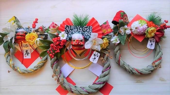 これは100均のしめ縄お正月飾りをアレンジしたものです。ベースができているので、短時間で作ることができます。子供さんと一緒に楽しく作るのもいいですね。  中央と左側 獅子舞、紙飾り、松、水引きが付いていたので、花、実、葉、キラキラパーツ、和風のリボンを足しました。  右側 真ん中のピンポンマムと紙飾り、松、水引きが付いていたので、その他の花、実、葉、キラキラパーツ、和風のリボンを足しました。