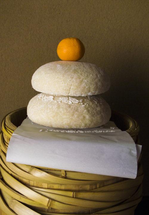 鏡餅は年神様(としがみさま)が宿る神聖なお供え物として、お正月に飾られるお餅です。まるく大小と大きさの違う餅が重なり、まるい餅の形の意味は、まるい鏡、円満な人間の魂を表しているなどと言われ、ウラジロ(裏白)というシダ植物の上にどっしりと座っているような安定感のある朗らかな様子です。新鮮な米をついて年の瀬から家の中にお正月飾りの主役として飾られ、固い餅である事にも「歯固め」という意味が込められ、固い物を食べれる丈夫な歯で元気に食べて、長寿を願い「歯固めの儀」として平安時代から長寿や健康を祈る儀式として受け継がれ現在まで続いている日本の文化です。鏡餅には年神様が宿り、年神様から「年玉(年魂)」という幸運を鏡開きの時に餅を割って分けた事から、現在の「お年玉」をお正月にもらう風習へと発展したと言われています。