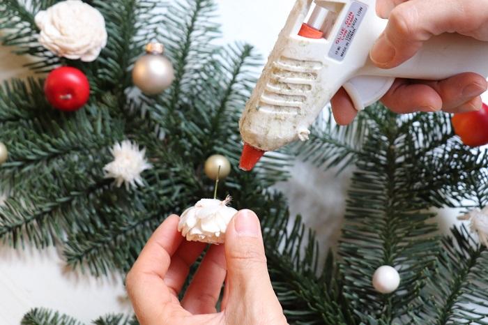 飾り付けするパーツの裏側にグルーを付けて、もみの枝に接着していきます。