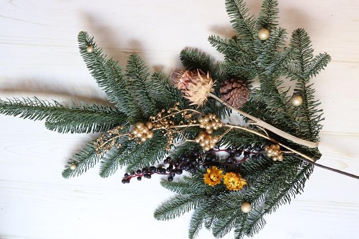 今度は、もみの枝を下向きに使ってスワッグ風壁飾りを作ってみたいと思います。  おおよそのバランスを考えて飾りを配置してみましょう。