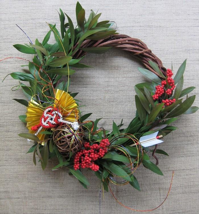 これは、ブラシの木(金宝樹)という常緑樹のフレッシュな枝を使ったお正月飾りです。しめ縄でなくリース台に飾り付けています。