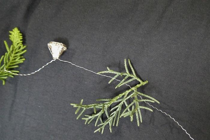 ユーカリは実の中心にワイヤーをくるりと巻き付けて、根元できゅっきゅっと捻って固定します。ワイヤーが真ん中を通っていればきちんと固定されます。この作業をワイヤーの長さの分だけ続けます。針葉樹の葉とユーカリの実、リューカデンドロンがランダムに繋がるように。