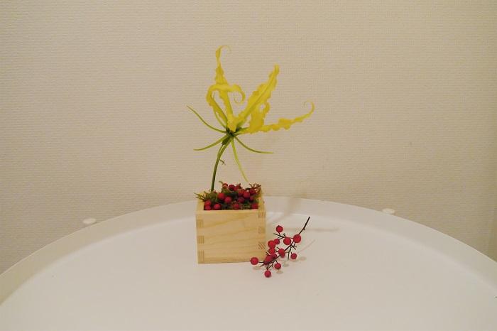 気取らずに玄関やリビングの空いたスペースに、さり気なく飾ってほしいアレンジメントです。新年に日本酒をいただいた枡で、ちょっと和モダンな花あしらいを楽しんでください。