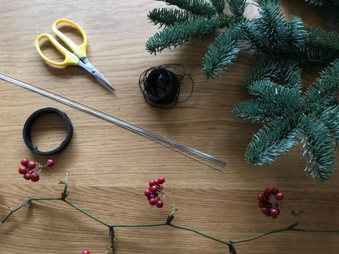 今回使う材料を準備してみましょう。もみの木の枝ですが11月の半ば頃から、お花屋さんにも出回りはじめます。値段はサイズにもよりますが1枝¥500~¥3,000くらいの値段で購入する事ができ、飾る場所の壁に合わせて枝の大きさを決めると、仕上がった時にスペースに対してバランスよく飾る事ができます。山帰来(サンキライ)の実も同じ時期に、お花屋さんで出回りはじめ、1枝に実のついた房が3~8房くらいついていますので、飾りたいボリュームに合わせて数枝購入するとよいと思います。1本から購入できますが5本まとめてで販売している事が多く¥300~¥1,500くらいの値段で購入できます。資材のスチールワイヤーとフローラルテープは、こちらはホームセンターや手芸店などでお取り扱いされています。購入前にお店へ問い合わせてから行くと安心ですね。