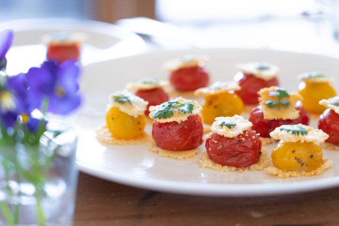 盛り付けは、薄く焼き上げたバルメザンチーズを器に敷き、その上にソテーしたミニトマトをのせます。最後にもう1枚バルメザンチーズをのせトマトをバルメザンチーズではさむ様に盛り付けます。最後にチャービルやイタリアンパセリ等を飾りつけしたら出来上がりです。  トマトは火をかけると甘みが増すので、トマト嫌いな方でも美味しくいただく事が出来ます。今回はカリカリに焼き上げたバルメザンチーズとジューシーなミニトマトの食感が最高の一品です。是非、お楽しみ下さい。