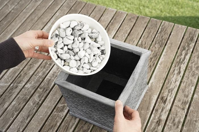 鉢の底に鉢底ネットを敷いて、鉢底石を器の底が見えなくなるくらい入れます。