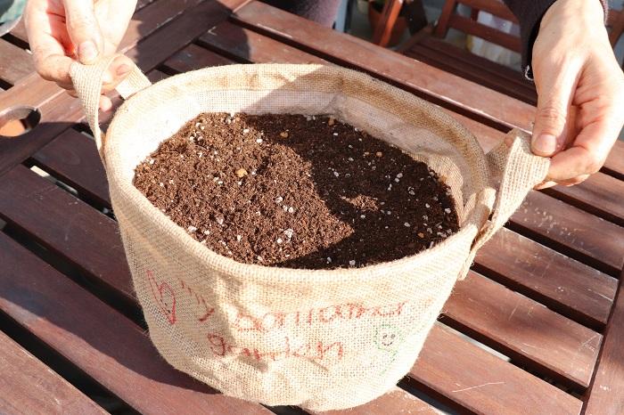 赤玉土の上に、野菜用の培養土を加えます。水やりの際に土や種が流れ出ないように、ウォータースペースを少し残して土を入れましょう。