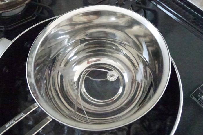 キャンドル芯を溶けたワックスに浸して、コーティングします。