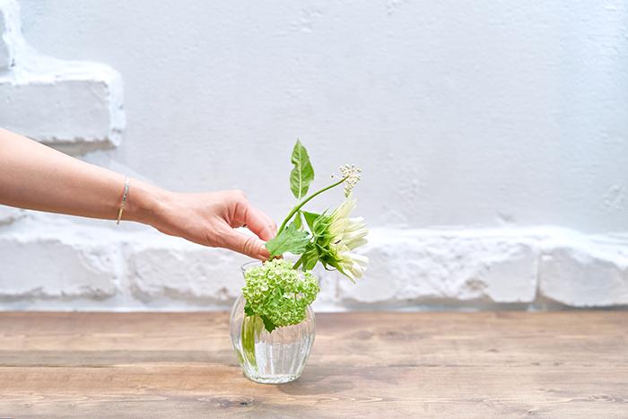 ヤマゴボウ、ビバーナム、ひまわりをそれぞれ花瓶の長さに合わせて切り、下部の葉をとる。ビバーナムは手前に添え、後方にひまわり、ヤマゴボウを生ける。