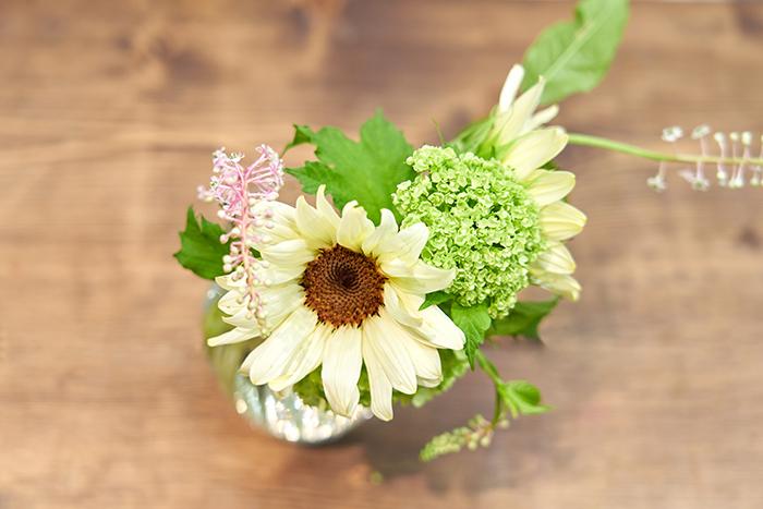 後方の隙間にもひまわりを生ける。下部や後方など、どの角度から見ても花が美しく見えるよう、全体の姿を意識する。