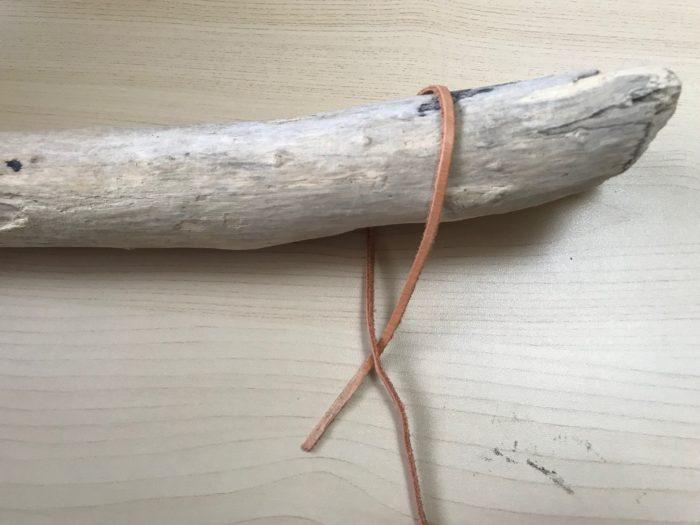結び方「ふた結び」  ふた結びは船乗りが船を結んだり荷物を結んだりする結び方です。一度覚えると色々なシーンで使う事が出来ます。  1.流木にぐるっと皮を回します。
