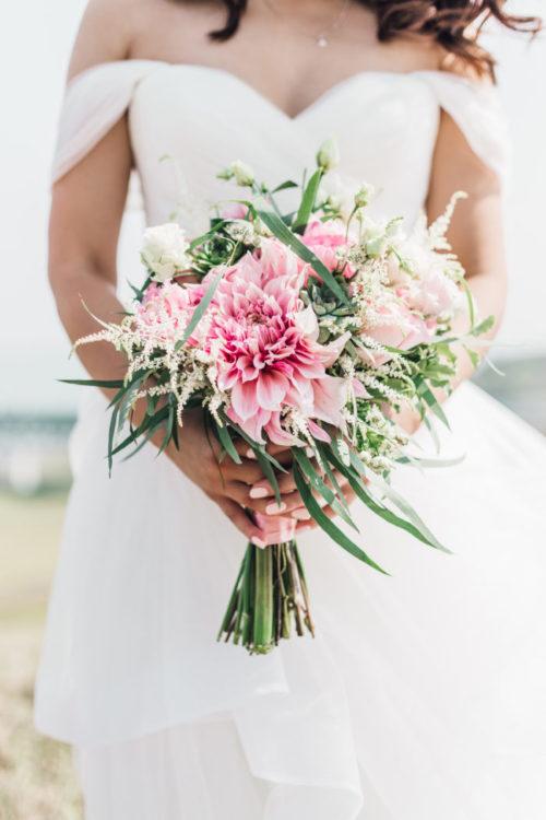 秋が開花時期のダリアは大小さまざまな種類があります。存在感のある大きめのダリアを主役にしたり、小さめの花を他の花と組み合わたせたりダリアの品種によって幅広いテイストに合わせることができる花材です。色も豊富にあるので、柔らかいピンクのダリアで上品な可愛らしさを演出したり、こっくりした深い赤のダリアでかっこ良い花嫁を引き立てたり様々な表情を作り出せます。花弁が沢山重なっている豪華な姿は洋風だけでなく和風のブーケにも使用されることもあります。