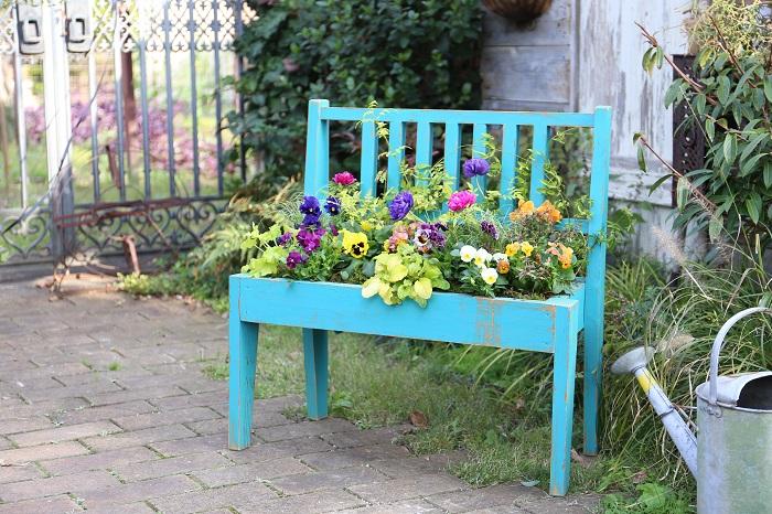 このベンチプランターは実はDIYが得意な社長のお手製です。植物を直接植込むことができ、他の色もお店で販売しています。  イエローやパープル、オレンジなどカラフルな春の草花の色彩をふんだんに取り入れた、楽しくなるような寄せ植えを作りました。玄関先や庭のフォーカルポイントにぴったりです。