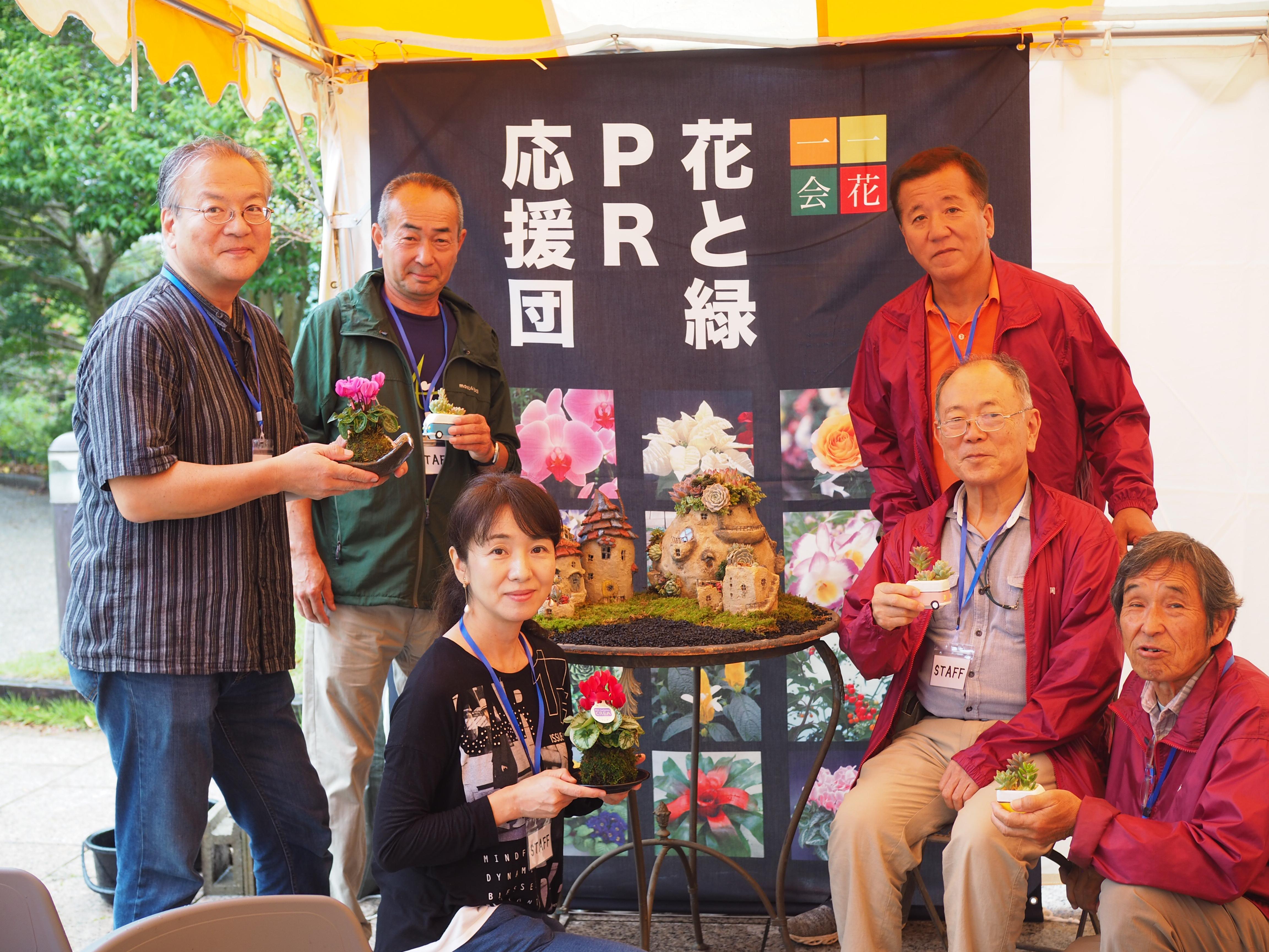 ミニシクラメンの苔玉を、犬塚和義団長(右から3人目)にレクチャーしてもらいました。  ちなみに使用するミニシクラメンは地元愛知の生産者・早川園芸さん(左から2人目)が丹精込めて育てた1級品です。